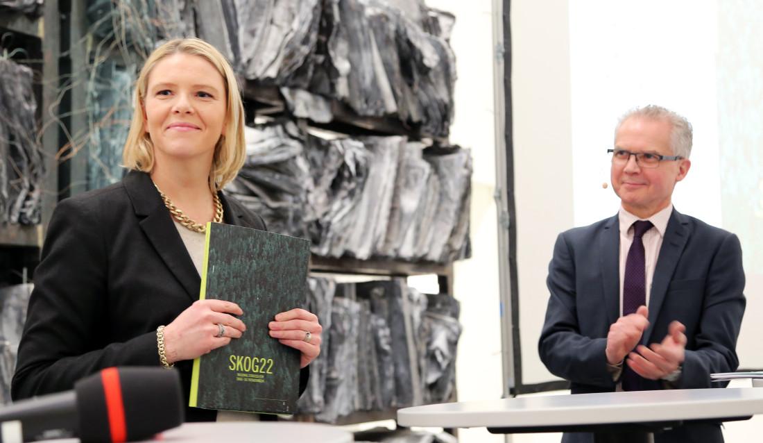 Landbruks- og matminister Sylvi Listhaug har akkurat mottatt Skog22-rapporten. Bak står en applauderende leder for utvalget, Gunnar Olofsson.