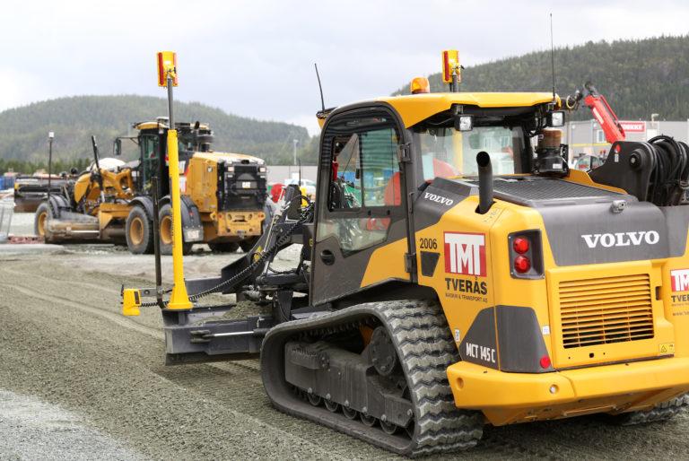 Maskinen er så lav at den kommer f.eks. lett inn i en parkeringskjeller, noe som ville vært vanskelig med en veihøvel (som f.eks. Cat-en i bakkant på bildet). Den gule boksen som er festet nederst til venstre over skjæret, er ultralydsensoren. (Foto: Runar F. Daler).