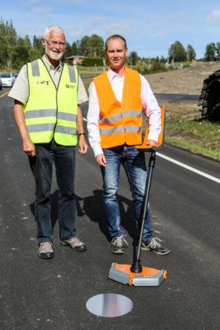 Stian Holte fra Holte Electronics og Matthias Herold fra MIT Mess- und Prüftechnik. Foran sonden ligger den runde aluminiumsplaten, eller reflektoren, som må ligge under asfalten for at målingen skal kunne utføres. (Foto: Runar F. Daler).