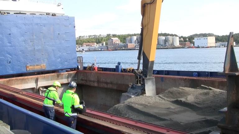Ronny Sørås fra NCC og Roald Fure fra Skanska inspiserer sanden som skal dekke fjordbunnen. (Foto: Robin Stenersen/NCC).