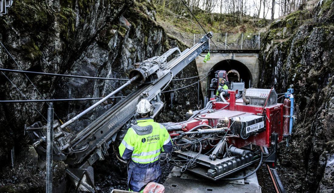 TRANGT: Ikke bare er det trangt til fjellveggen på begge sider, men kjøreledningen befinner seg bare noen få meter over riggen. Men Truls Omland Aasheim styrer med stø hånd mens Bård Magnus Dalen følger nøye med. (Foto: Runar F. Daler).