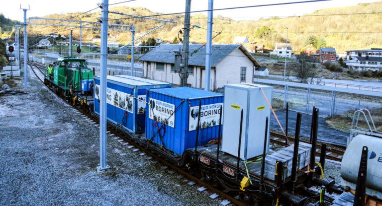 TOGET: Det tyskproduserte lokomotivet trekker vogner som bl.a. inneholder kompressorer, vanntank, kran, borerigg, mannskapsbrakke og et eget toalett. Den største containeren på bildet fungerer som mannskapsbrakke. (Foto: Runar F. Daler).