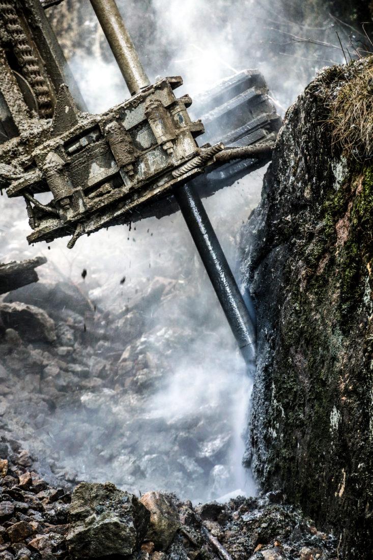 TØFT: Her bores det med vanlig fjellkrone på en seks meter lang borstang. Opp av hullet spruter en blanding av borkaks og vann som sprer seg med vinden, og fotografen har et svare strev med å få tørka av kameralinsa. (Foto: Runar F. Daler).