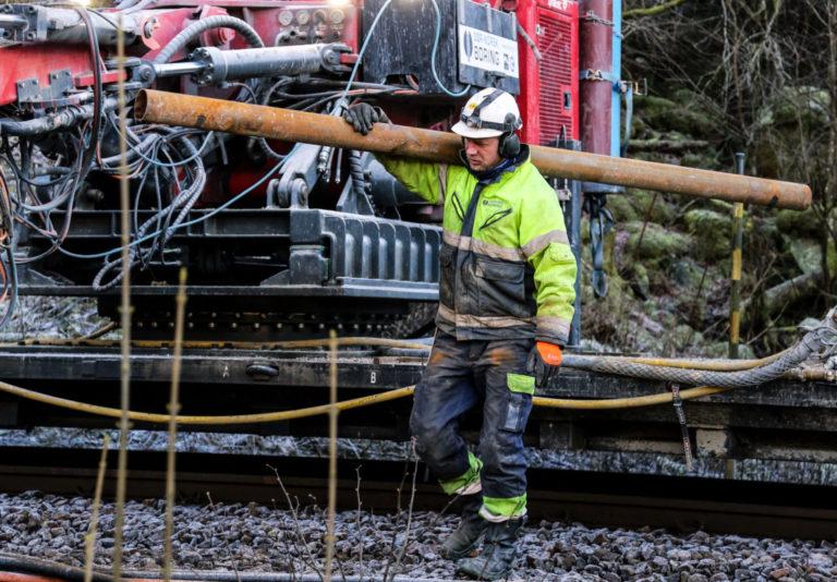 LØFT: Rørene som bores ned i løsmassene er tre meter lange og må skjøtes to og to for å oppnå den nødvendige lengden på seks meter. Her henter Bård Magnus Dalen et nytt rør. (Foto: Runar F. Daler).
