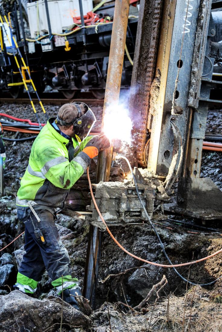 SVEISING: Når stålrøret er nesten helt nede i grunnen, sveises det på et nytt rør, slik at totallengden blir seks meter. (Foto: Runar F. Daler).