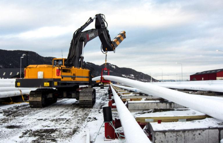 En av 70-tonnerne med kran på bommen flytter litt på de kilometerlange oljerørene. (Foto: Mardahl Maskin).