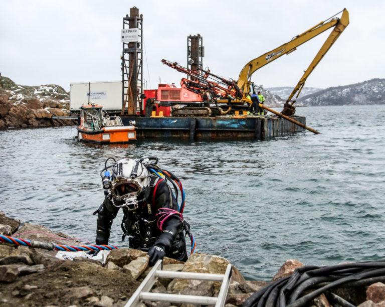 DYKKEREN: Knut Wetaas fra dykkerfirmaet O.E. Hagen AS kommer opp igjen fra vannet etter å ha vært nede og klargjort undervannssalven. (Foto: Runar F. Daler).