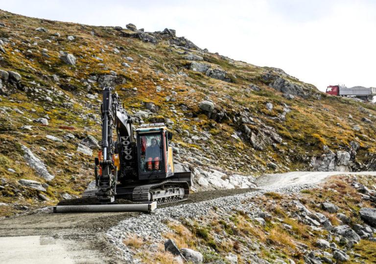 På vei opp den smale, svingete adkomstveien, ble vi møtt av en 15-tonns Volvo-graver med avretterbjelke, som var i ferd med å avrette og komprimere et nytt slitelag på veien. (Foto: Runar F. Daler).
