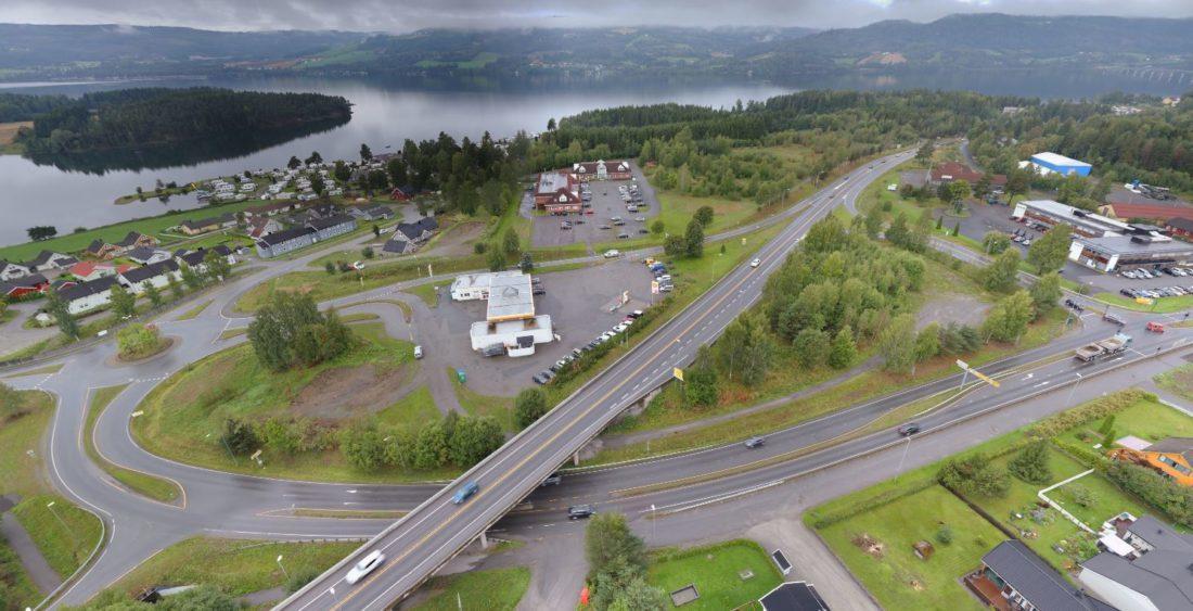 Bildet viser dagens E6-kryss i Moelv. E6 kommer inn fra Hamar/Brumunddal nederst i bildet og fortsetter i retning Lillehammer øverst til høyre i bildet. Fylkesvei 213 (Storgata) passerer under E6. Moelv sentrum ligger til høyre for bildet. (Foto: Nordic Skytech AS)