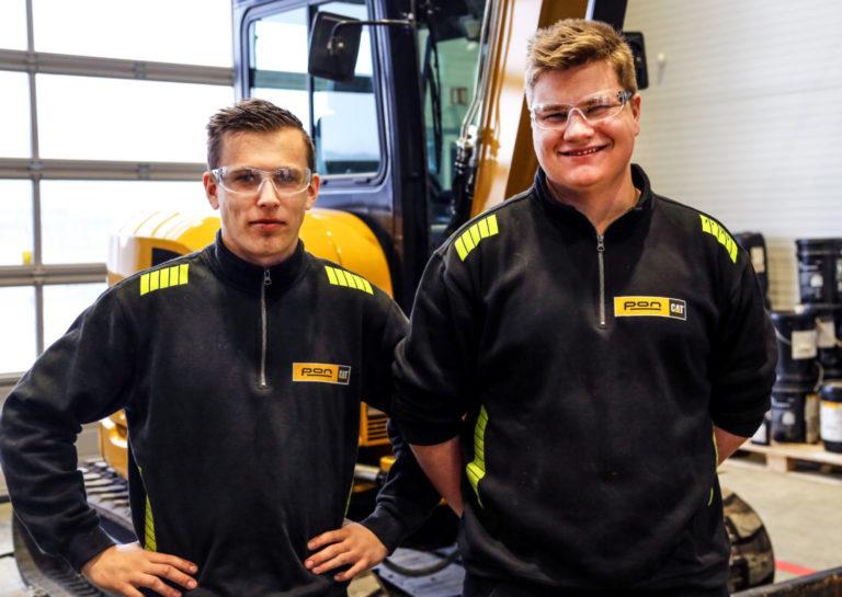 TRIVES: Lærlingene (f.v.) Anders Carstensen (19) og Kristoffer Mathisen (19) har vært i Pon siden juni i år, og trives veldig godt. Anleggsmaskinen møtte dem på verkstedet, hvor Anders fiksa en lekkasje på en tiltrotator, mens Kristoffer pussa og flekklakkerte på en beltegraver. (Foto: Runar F. Daler).