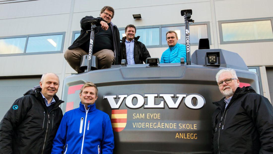 FORNYØD GJENG: Sam Eyde vgs. har fått maskinstyring fra Topcon på tre av sine nye Volvo-gravere, ved hjelp av en gave fra OKAB/MEF, samt meget gunstig pris av Topcon. Her er gjengen samlet foran og oppå den ene beltegraveren, en Volvo EC140EL. Foran fra venstre: Frank R. Nygård (OKAB), Kjell Arvid Løyning (Volvo Maskin), Odd Arne Meyer Sjøberg (landslinjekoordinator). Oppå maskinen, fra venstre: Lars Ole Hansen (Sam Eyde vgs.), Roar Heiland (Norsecraft) og Per Christian Andersen (Norsecraft). (Foto: Runar F. Daler).