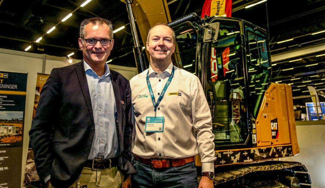 Pon Equipment, her representert ved Erik Sollerud (adm. dir) og Dagfinn Sand (ansvarlig for kompakte maskiner) slapp en stor nyhet på Arctic Entrepreneur: Maskinen i bakgrunnen, en Cat 307.5, skal ombygges tilen batterelektrisk Z-line. (Foto: Runar F. Daler).
