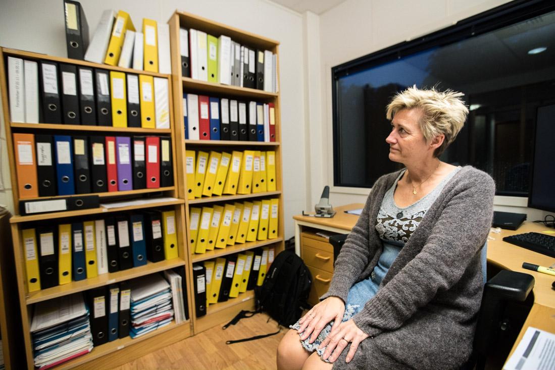 Mona Mortensen, daglig leder i Repstad Anlegg AS. Veggen med permer er dokumentasjon til tvistesaken mot Statens vegvesen.