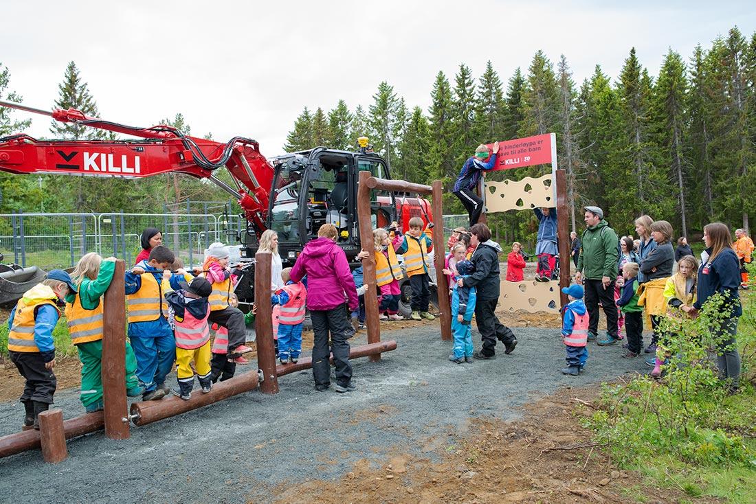 Lekende barn og rød gravemaskin