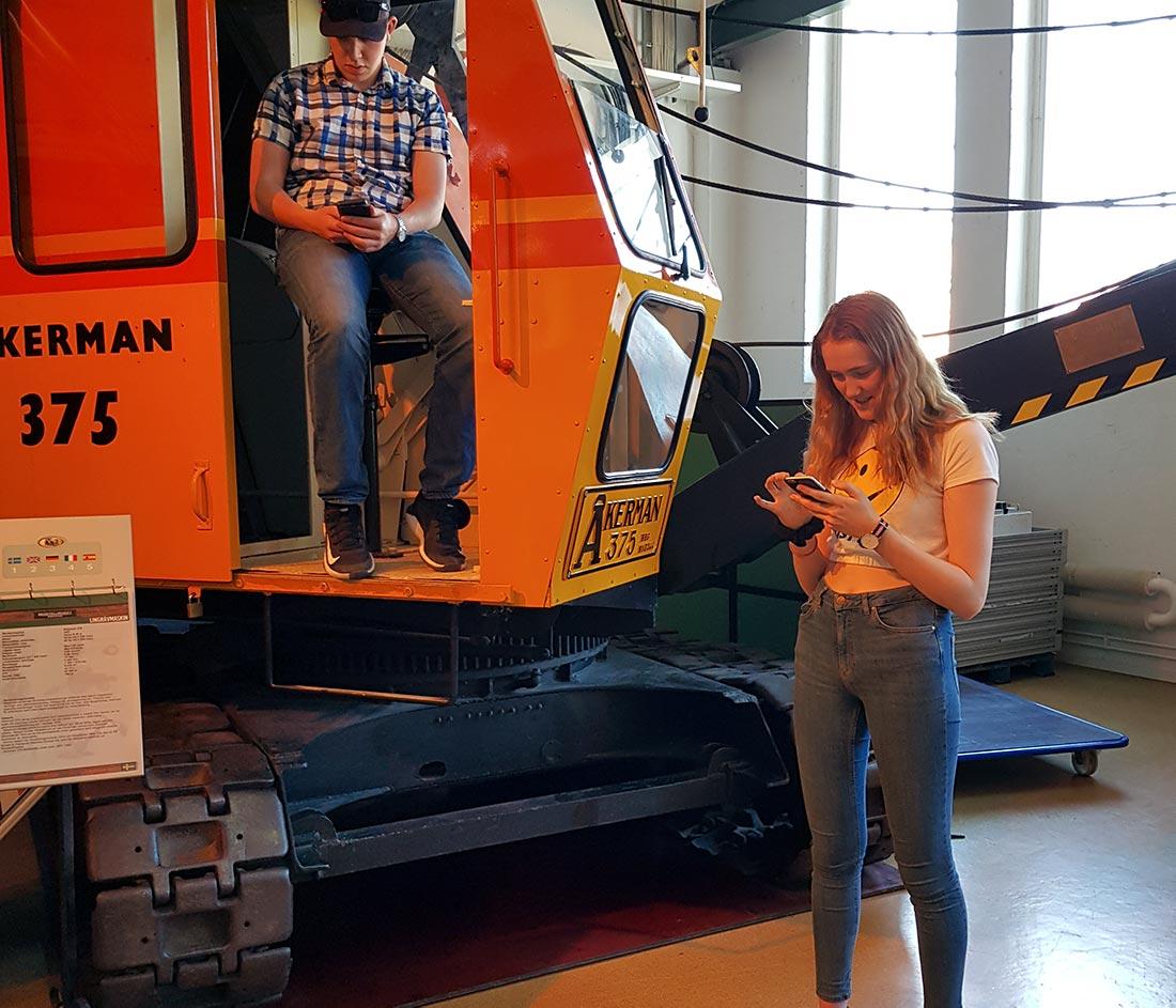 Gammel gravemaskin og to ungdomme med mobil