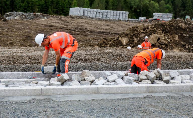 STEINLEGGING: Her legges steiner rundt en av de nye rundkjøringene. Det er Landskapsentreprenørene som utfører jobben. (Foto: Runar F. Daler).