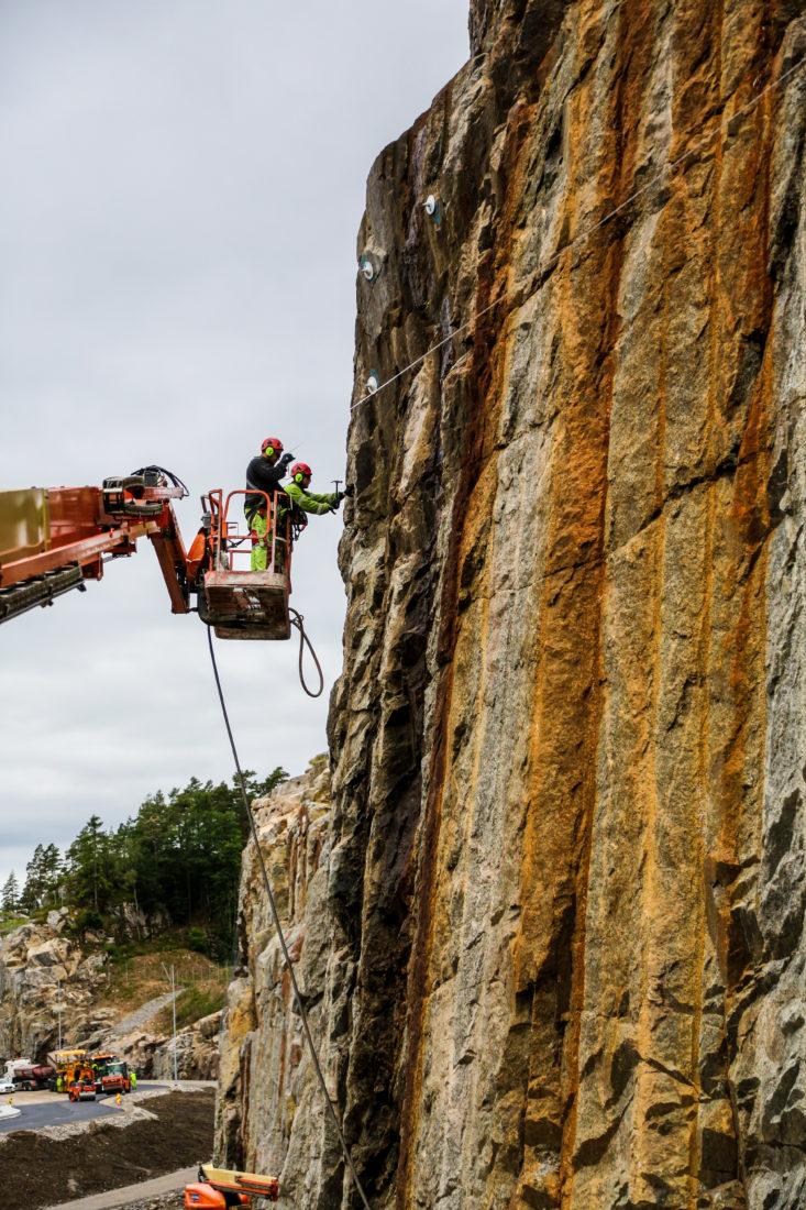 FJELLSKJÆRINGER: Det er hele 8000 løpemeter fjellskjæringer på prosjektet, og de høyeste er 38 meter. Det sikres både med bolter og steinsprangnett. (Foto: Runar F. Daler)
